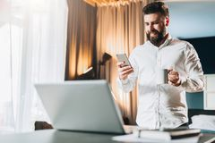 Young smiling bearded businessman standing near table in front of laptop, using digital tablet, drinking coffee. Man checks e-mail, blogging, chatting. Online Royalty Free Stock Image