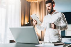 Young smiling bearded businessman standing near table in front of laptop, using digital tablet, drinking coffee. Man checks e-mail, blogging, chatting. Online Stock Photography