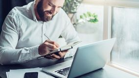 Young smiling bearded businessman in white shirt sitting at desk in front of laptop, making notes in notebook. Freelancer works remotely. Student learning Stock Photography