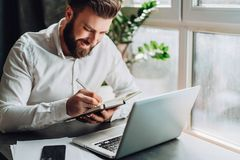 Young smiling bearded businessman in white shirt sitting at desk in front of laptop, making notes in notebook. Freelancer works remotely. Student learning Stock Photos