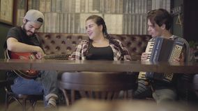 Young smiling bearded man playing guitar in the bar, his friend playing accordion while attractive plump woman sitting. Young smiling bearded man playing guitar stock video footage