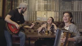 Young smiling bearded man playing guitar in the bar, his friend playing accordion while attractive plump woman sitting. Young smiling bearded man playing guitar stock footage