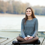 Young smiling beautful brunette woman with her smartphone outdoors Royalty Free Stock Photos