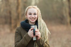 Young smiling beautiful blonde hipster woman posing with thermos cup cold season outdoors Royalty Free Stock Images