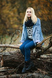 Young smiling beautiful blonde woman in jeans, scarf, and sweater, sitting on logs in autumn forest Stock Photos