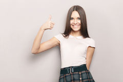 Young smiling beautiful brunette woman posing indoors against wall with thumbs up gesture Royalty Free Stock Photography