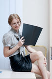 Young smiling beautiful businesswoman with black folder sitting Stock Photos