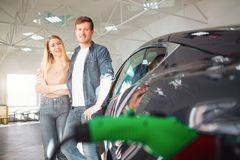 Young smiling family buying first electric car in the showroom. Environmental protection. Modern green vehicle with stock image