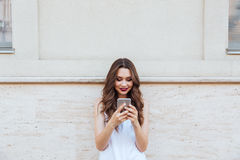 Young smiling beautiful girl using her phone outdoors Stock Photo