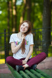 Young smiling beautiful redhead woman in red jeans sneakers shirt sitting on bench touching her hair blurry forest park background Stock Photo