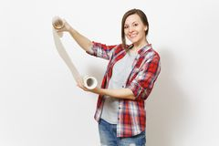 Young smiling beautiful woman in casual clothes holding unrolled wallpaper roll isolated on white background. Instruments, accessories, tools for renovation stock photos