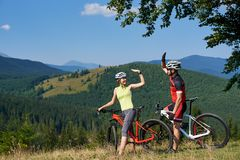 Young smiling bikers couple, man and woman, standing with bikes on grassy hill under big tree stock image