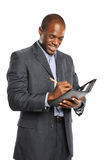 Young smiling black businessman taking notes Royalty Free Stock Photography