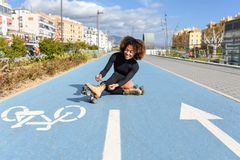 Young smiling black girl sitting on bike line and puts on skates. Woman with afro hairstyle rollerblading on sunny day Royalty Free Stock Photo