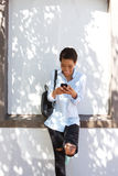 Young smiling black woman with mobile phone and bag Stock Image