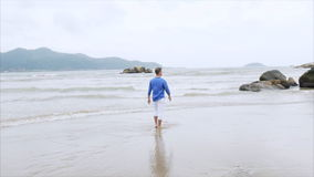 Young smiling blond man in a blue shirt and white pants walking on the beach near large stones, back view stock footage