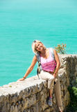Young smiling blond sitting on stone wall Royalty Free Stock Photos