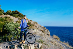 Young smiling blond woman with the bike standing on a rock. Attractive young smiling blond woman with the bike standing on a rock Royalty Free Stock Images