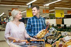Young smiling blond woman with her husband buying potatoes with Royalty Free Stock Photography