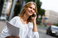 Young smiling blond woman with mobile phone and papers stock images