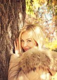 Young smiling blonde woman portrait, posing in autumn  park, dressed in jacket with fur hoodie. Royalty Free Stock Photo
