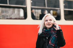 Young smiling blonde woman talking on the phone on the background of the tram. Outdoor portrait of a girl. Young smiling blonde woman talking on the phone on Royalty Free Stock Photos