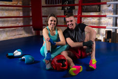 Young smiling boxing couple sitting near lying boxing gloves and stock photography