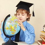 Young smiling boy in academic hat looks at a globe among old books Stock Image