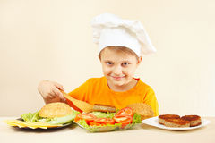 Young smiling boy in chef hat puts meat on hamburger Royalty Free Stock Images