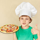 Young smiling boy in chefs hat with cooked appetizing pizza Royalty Free Stock Images