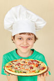 Young smiling boy in chefs hat with cooked homemade pizza Royalty Free Stock Image