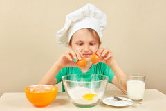 Young smiling boy in chefs hat pours eggs for baking cake Stock Photo