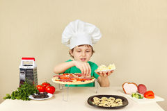 Young smiling boy in chefs hat puts a grated cheese on pizza crust Royalty Free Stock Image