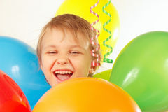 Young smiling boy with festive balloons and streamer Royalty Free Stock Photo