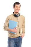 A young smiling boy with headphones holding a book Stock Photography