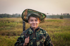 Young smiling boy with hunting shotgun standing at green field during sunset Stock Photos
