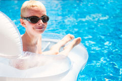 Young smiling boy laying on a floating mattress in a swimming po Stock Photography