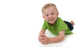 Young smiling boy laying on his stomache. Young happy boy in a green shirt on a white background Royalty Free Stock Photos