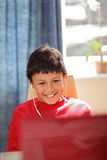 Young smiling boy looking at a computer Stock Images