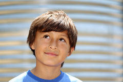 Young smiling boy looking up. Young boy in front of metal water tank Stock Image