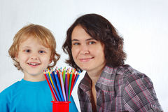 Young smiling boy with mother with color pencils Royalty Free Stock Photos