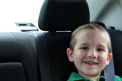 Young smiling boy sitting in car seat royalty free stock photos