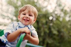 Young Smiling Boy Sitting Outdoors on Playground Stock Photos