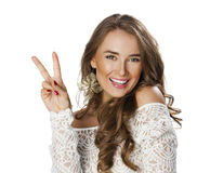 Young smiling brunette woman showing victory or peace sign Stock Images