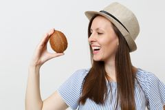 Young smiling brunette woman in summer hat hold in hands coconut or exotic coco nut isolated on white background. Proper stock images