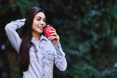 Young smiling woman holding the cup of coffee. Young smiling brunette woman, wearing blue denim shirt and holding the red cup of coffee stock photography