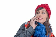 Young smiling brunette woman with a winter cap using smartphone. A young smiling brunette woman with a winter cap using smartphone Stock Images