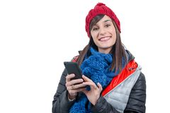 Young smiling brunette woman with a winter cap using smartphone. A young smiling brunette woman with a winter cap using smartphone Stock Photography