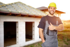 Young smiling builder gesture with his thumb up. Toned Royalty Free Stock Photo
