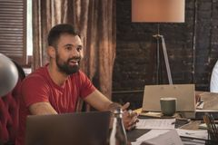 Young smiling business man with beard sitting in start up dark office Royalty Free Stock Image